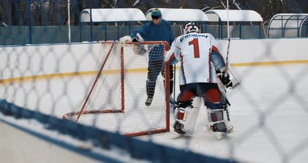 hockey rink : Two boys in ice hockey uniforms playing hockey on ice rink. Stock Footage