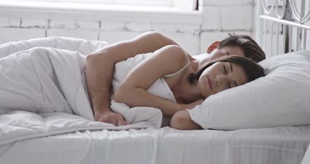 quarto doméstico : Young adult couple sleeping on the bed in bedroom Vídeos