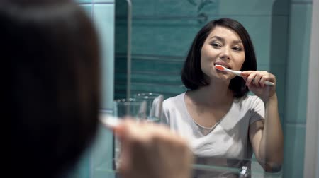 escovação : Portrait of attractive woman brushing teeth in bathroom and looking in the mirror at reflection. healthy teeth. Vídeos