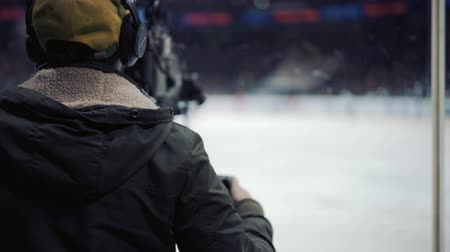 videocamera : A professional videographer at a hockey game.
