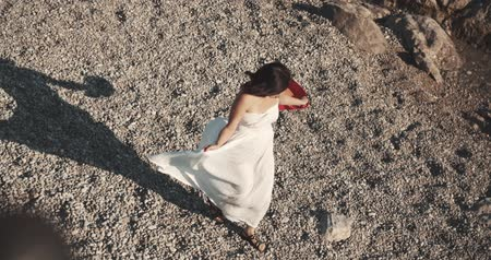 rejtekhely : the Asian girl walks on a stony beach in a white dress