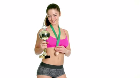 vencedor : Happy sports woman holding winner cup and a medal isolated