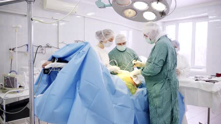 szoba : Team of surgeon in uniform perform operation