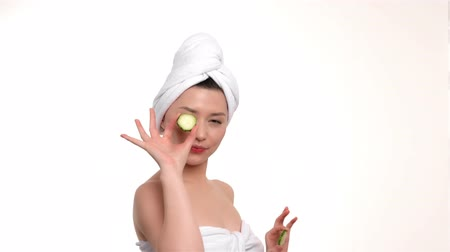 pepino : Spal girl covering her eyes with a slices of a cucumber