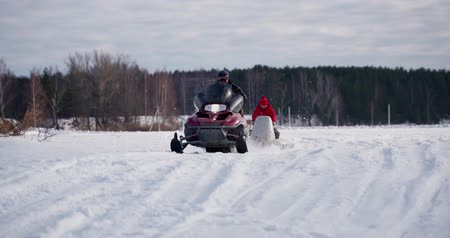 jump away : Young man with his brother on snowmobile