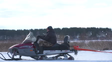 jump away : Young couple on snowmobile sunny day winter Stock Footage