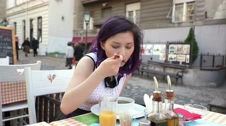 zupa : A woman eating soup in a restaurant