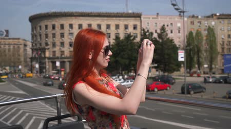 double happiness : young woman photographing the city from an open top bus