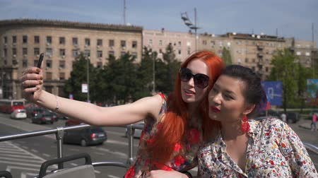 double happiness : Two young women taking selfie on an open top bus Stock Footage