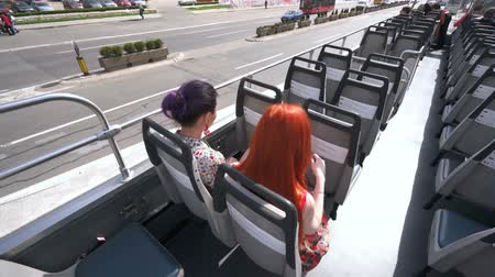 double happiness : Two young pretty women listening audiotape on an open top bus