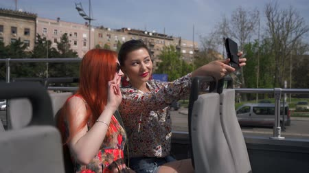 double happiness : Two pretty women taking selfie on an open top bus