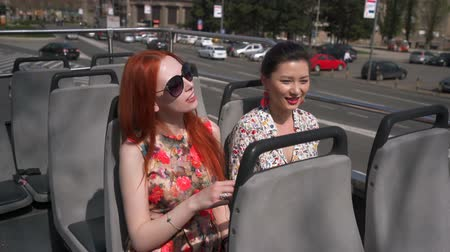 double happiness : Young sexy women listening audiotape on an open top bus Stock Footage