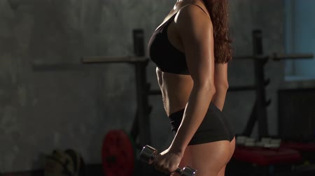 fit : Fitness girl with dumbbells in dark gym Stock Footage