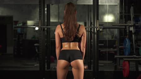 ginástica : Fitness girl with dumbbells from behind