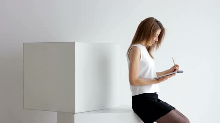 брюнет : Young woman sitting on cubes with papers