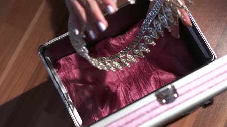 buried treasure : hands locking a briefcase with diadem