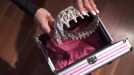 srebro : female hands locking a briefcase with diadem