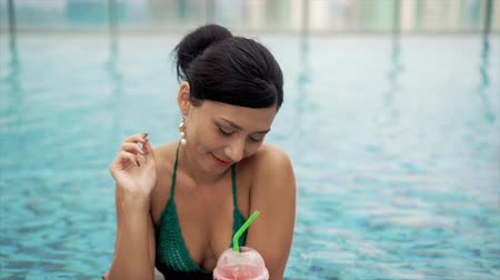 luxo : happy smiling woman drinking cocktail in pool