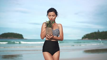 ananász : Girl drinking cocktail in pineapple on the beach Stock mozgókép