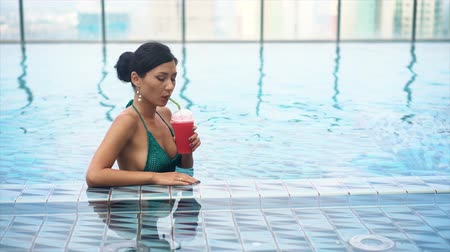 luxo : young pretty sexy girl drinking cocktail in pool Stock Footage
