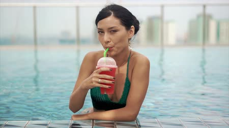 luxo : happy smiling girl drinking cocktail in pool Stock Footage
