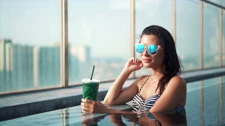luxo : Asian smiling woman drinking cocktail in pool Stock Footage