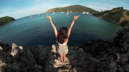 стоять : Young girl standing on a rock with raised hands Стоковые видеозаписи