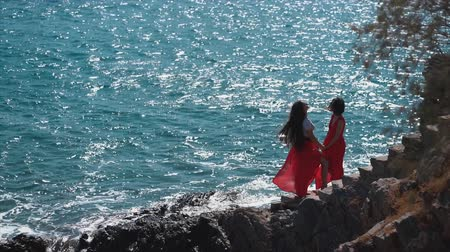 leszbikus : Girls in red dresses together at ocean cliff beach