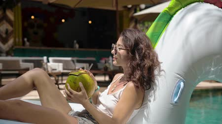 ginástico : Woman in pool drinking a coconut fruit Stock Footage