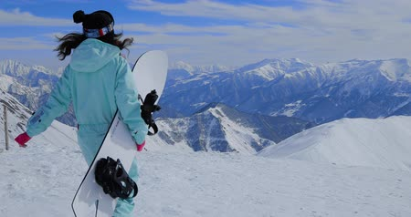 スノーボード : Girl snowboarder stands with snowboard on mountains top 動画素材