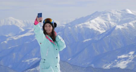 narciarz : Female snowboarder using her smart phone, taking pictures in the mountains