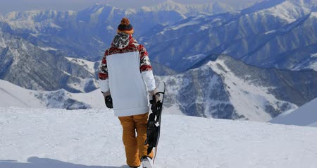 hevesli : Enthusiastic snowboarder holding his snowboard while walking at the top of a mountain
