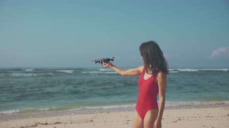 Beautiful woman playing drone on the beach
