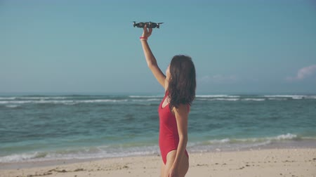 Asian woman playing drone on the beach Stock mozgókép