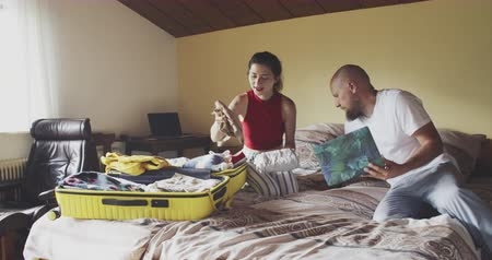 Couple packing suitcase in bed and using laptop