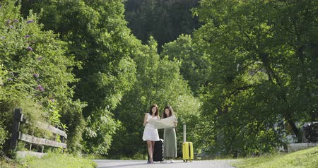 Two girls standing with luggage and map Stock mozgókép