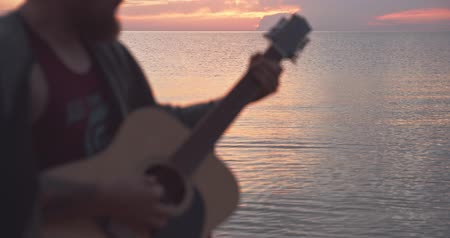 Man in bokeh playing guitar at seaside during sunrise.