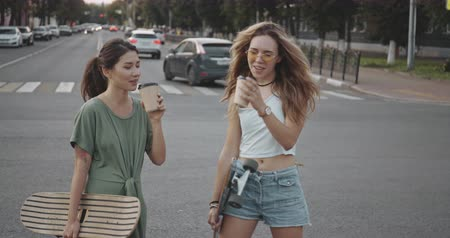 Two girls have fun together with skate board