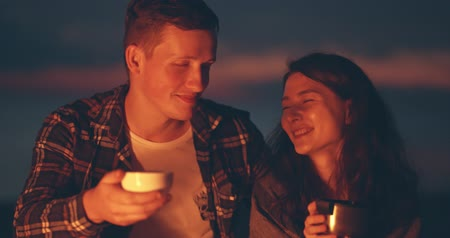 kamp ateşi : young couple drinking hot beverage near bonfire Stok Video