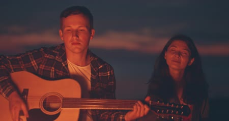 hořlavý : Portrait of a young couple sitting with guitar near bonfire