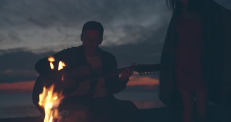 A Man playing guitar and girl dancing near bonfire Stock mozgókép
