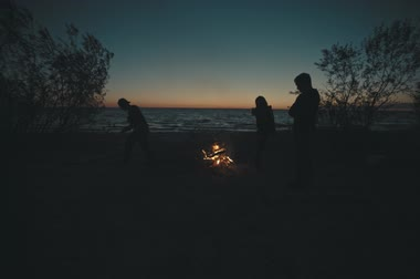accent : People making a bonfire at sunset