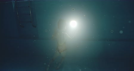 nadador : Underwater dramatic shot of woman in swimming pool