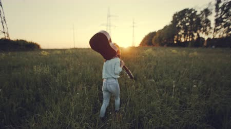 slow motion. beautiful girl playing the guitar in a wheat field