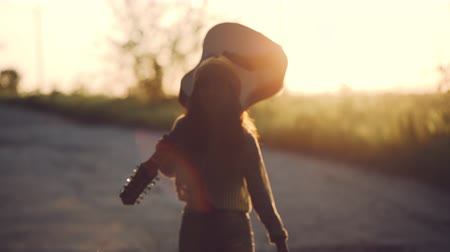 hippie : slow motion. beautiful girl playing the guitar in a wheat field