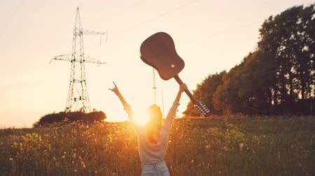 Happy woman in sunflower field playing on guitar and singing. Summer girl in cowboy straw hat. Caucasian young lady jumping and have fun with raised hands. Slow motion. Little guitar. music concept. Stock mozgókép