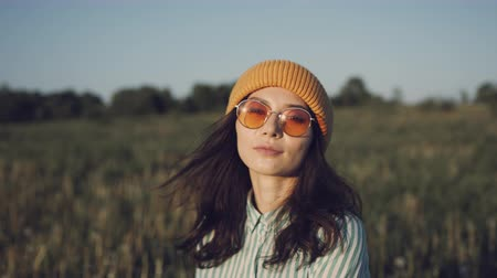 stanovena : Cute asian girl standing in the wheat field during sunset as the wind blows her hair, looking at camera - close up portrait shot 4k footage