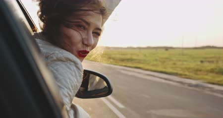 emperrado : The beautiful girl stuck her hand out of the car window and smiles in sunny weather. slow motion Vídeos
