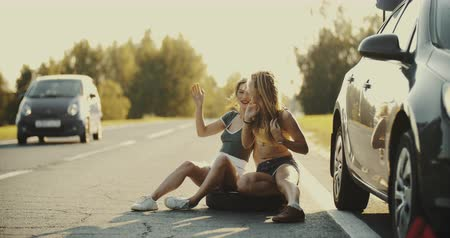 beira da estrada : A young couple are hitchhiking standing on the road. A man and a woman stop the car on the highway with a sign Anywhere Stock Footage