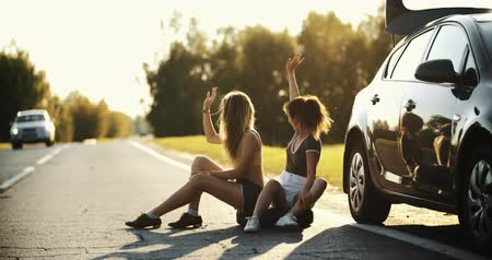 Pretty young woman in trouble hitch-hiking on the country road on hot sunny day. Portrait of stressed girl waving hands in air trying to get help having problem with broken car. Car issue.